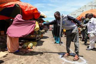 A Somali woman sells fruits to a customer standing at a social distancing marker in late April in Mogadishu, Somalia, during the COVID-19 pandemic.