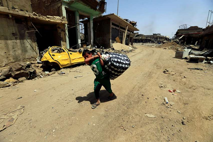 A boy carries his belongings in Mosul, Iraq, July 23. Some Iraqi Christians who are making their slow return to ancestral lands say it will take time to rebuild their lives and trust of those who betrayed them.