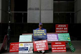 Abuse victim Darren Chalmers sits on a bench with numerous placards outside the venue for Australia's Royal Commission Into Institutional Responses to Child Sexual Abuse in Sydney March 2016.