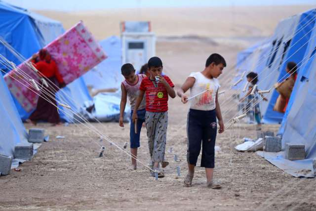 Iraqi refugees are seen in a camp near the northern city of Irbil June 12. Hundreds of thousands of people who have fled their homes in Mosul are left without access to aid, officials said. Christians from the city say they were targeted long before Iraq i security forces abandoned the major political and economic hub.