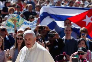 "A man holds Cuba's flag in the crowd as Pope Francis arrives to lead his general audience in St. Peter's Square at the Vatican in this photo dated May 27, 2015. Bishop Wilfredo Pino Estevez said that Pope Francis' visit to Cuba is a sign of his closeness to the nation's people at a time they ""breathe the air of hope"" that relations with the United States will improve"