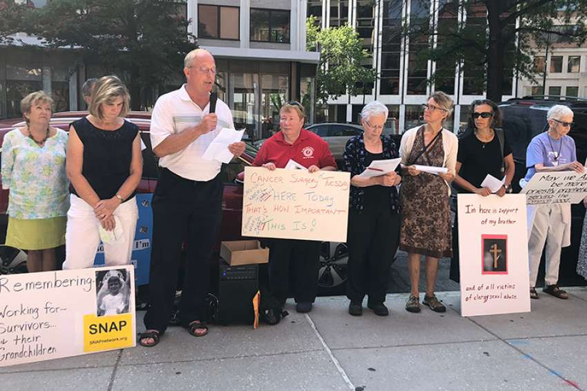 David Lorenz, holding the microphone, addresses a crowd gathered outside the Cathedral of St. Matthew the Apostle in Washington Aug. 26. Joined by Catholics who showed up to support sex abuse victims, Lorenz, a survivor of clergy abuse, called on Cardinal Donald W. Wuerl to resign.