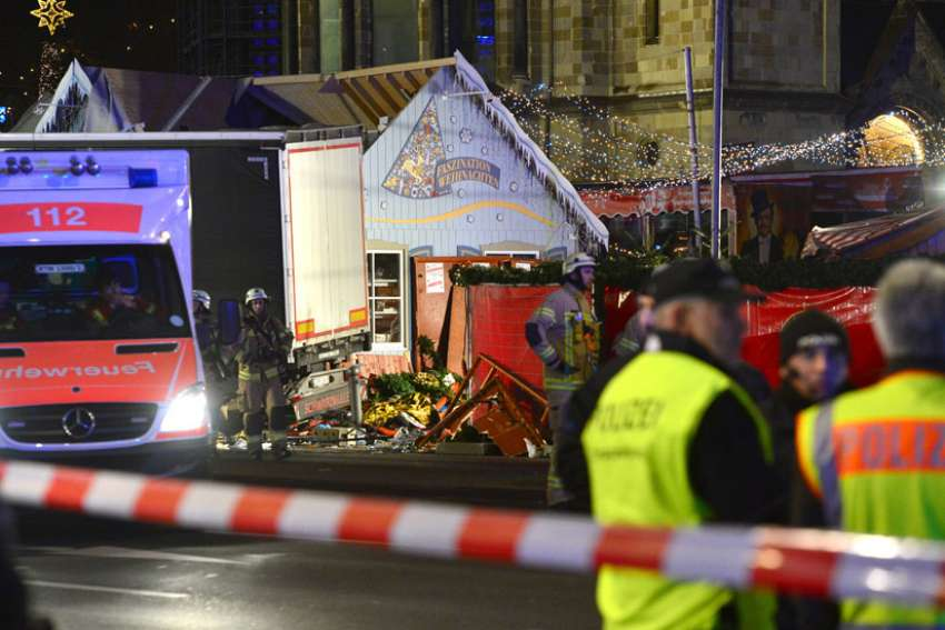 Rescue workers inspect the scene where a truck crashed into a Christmas market in Berlin Dec. 19. The terrorist attack killed at least a dozen people and injured nearly 50 as it smashed through tables and wooden stands.