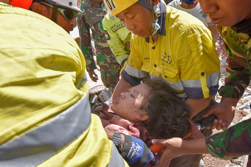 Rescue workers and soldiers carry a woman Aug. 7, who survived after being trapped in rubble following an earthquake on Lombok, Indonesia. At least 105 people have been confirmed dead after the magnitude 7 earthquake Aug. 5, a week after another powerful quake killed more than a dozen people.