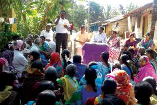 A group of  villagers in India listen to a Lok Manch speaker as he educates them on their rights under the National Food Security Act.