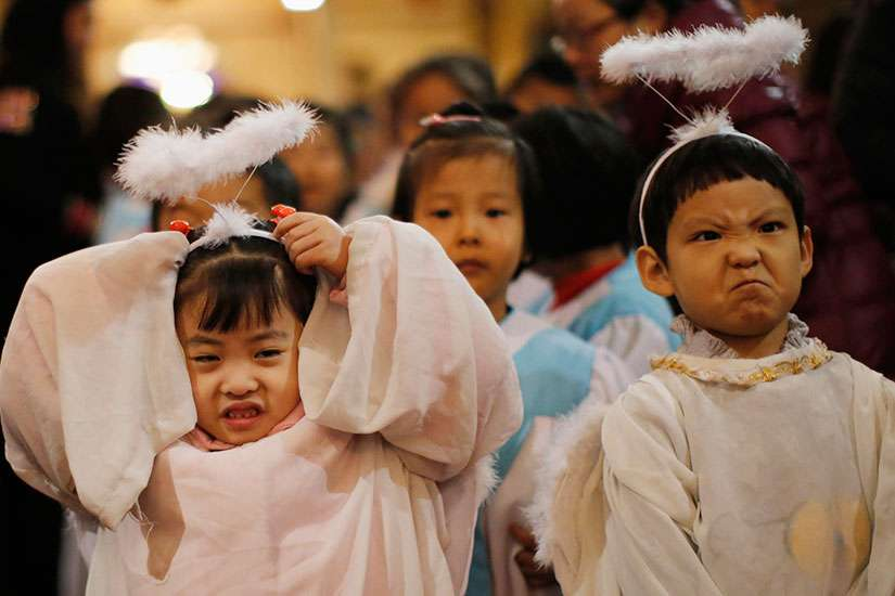 Children dressed as angels react as they attend Christmas Mass at a Catholic church Dec. 24.