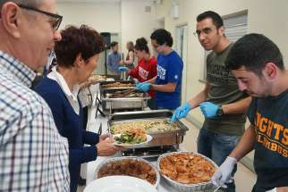 Husam Al Dakhil and his cousin Bahaa Hraiz serve a Syrian buffet. The cousins came to Canada a little more than a year ago. Now Holy Redeemer parish has found sponsors for their parents and siblings.