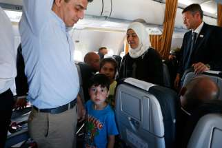 Syrian refugees walk though the aisle of Pope Francis' flight from the Greek island of Lesbos to Rome April 16, 2016. The pope concluded his one-day visit to Greece by bringing 12 Syrian refugees to Italy aboard his flight.