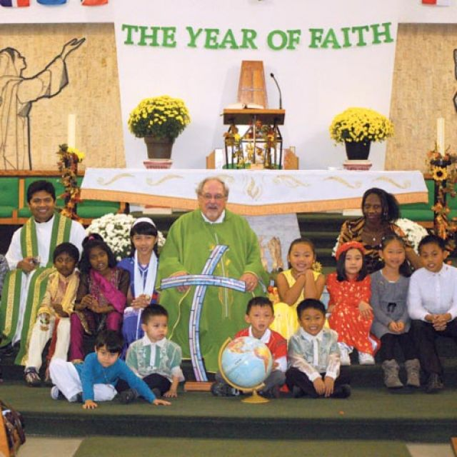 Fr. Massey Lombardi sits with a few children clad in the traditional garments of their heritage following the Oct. 14 Mass that kicked off the Year of Faith at Toronto's St. Wilfrid's parish.