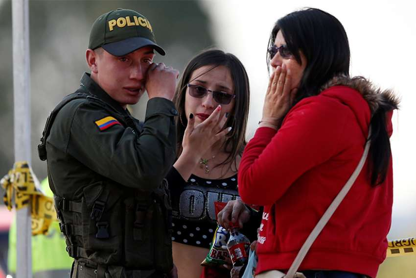 A police officer and two women wipe away tears Jan. 17, 2019, close to the scene where a car bomb exploded in Bogota, Colombia.