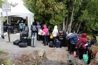 A group of Haitians wait to cross the U.S.-Canada border into Quebec from New York in late August 2017.