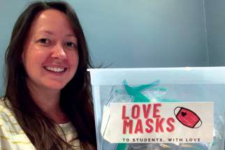Toronto teacher Rachel Thomas holds a bin full of Love Masks, masks that will be provided to students who need them when they return to school this month.