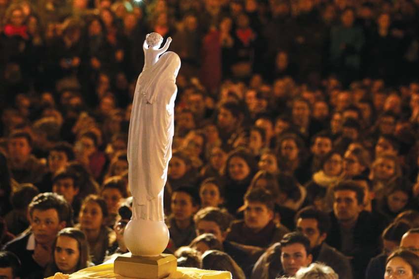 People stand in front of a statue of Our Lady of Notre Dame during a vigil near Notre-Dame Cathedral April 16, a day after a fire destroyed much of the church's wooden structure.