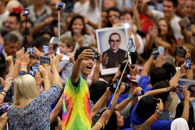 An audience member takes a selfie of himself with a photo of Blessed Oscar Romero behind him as Pope Francis arrives to lead his general audience in Paul VI hall at the Vatican Aug. 3. Bishops from Panama say Blessed Romero is an example of faith for youths.