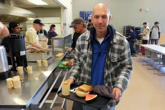 Bishop Donald J. Bolen of the Saskatoon, Saskatchewan, picks up breakfast at Saskatoon Friendship Inn June 18, after spending the night in a city park as part of the Sanctum Survivor homelessness challenge. He was one of 10 community leaders and celebrities who participated in the 36-hour event.