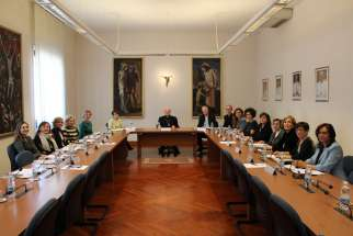 "Cardinal Gianfranco Ravasi, center, and Bishop Paul Tighe pose at a 2019 meeting of the Women's Consultation Group at the Vatican. The 20 members of the group, Catholics, other Christians and members of other faiths, met online Oct. 7 for a webinar reflecting together on Pope Francis' 2013 exhortation, ""The Joy of the Gospel."""