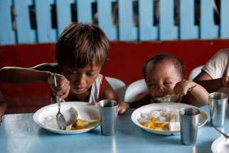 "A boy and his younger brother eat their free meals during a feeding program in late May at a slum area in Manila, Philippines. Pope Francis denounced widespread hunger due to wasted food as a symptom of a ""throwaway culture"" and called for greater effort to build a worldwide ""culture of encounter and solidarity"" instead."