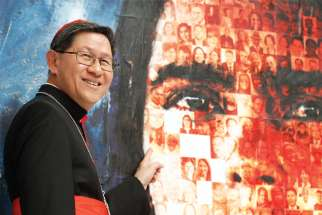 "Philippine Cardinal Luis Antonio Tagle, president of Caritas Internationalis, points to a photo of his maternal grandfather on a mosaic created for the 2019 general assembly of Caritas Internationalis. Tagle said Caritas must push a ""politics of communion."""