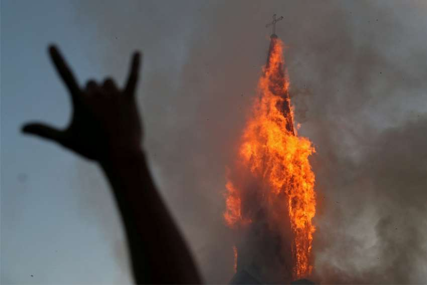 A protester gestures while a church is set on fire during a demonstration against Chile's government in Santiago Oct. 18, 2020, the one-year anniversary of the protests and riots that rocked the capital in 2019. The current protests occurred a week before a referendum on whether to ditch a dictatorship-era constitution.