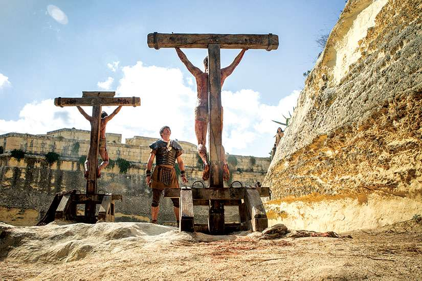 In Risen, a Roman soldier stands before the crucified Christ. Joseph Fiennes' character undergoes a transformation as he leads the manhunt for Christ's body after the Resurrection.