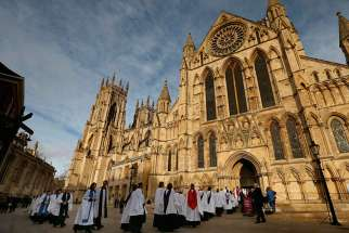 Members of the clergy enter York Minster before a service to consecrate the Rev. Libby Lane as the first female bishop in the Church of England, in York, northern England, on Jan. 26, 2015.