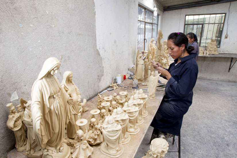 A woman works on a small statue of Pope Francis at the workshop of Ecuadorean sculptor Ramon Guato in Quito June 12. Guato, a sculptor of religious figures, has prepared about 2,000 figures to be sold at Catholic libraries ahead of the upcoming visit by Pope Francis to Ecuador in July.