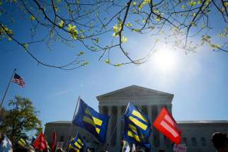 Supporters for same-sex marriage stand outside the U.S. Supreme Court in Washington April 28.The high court began hearing arguments in cases involving four states that bar same-sex marriage.