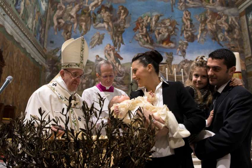 Pope Francis baptizes one of 28 babies in the Sistine Chapel at the Vatican Jan. 8.
