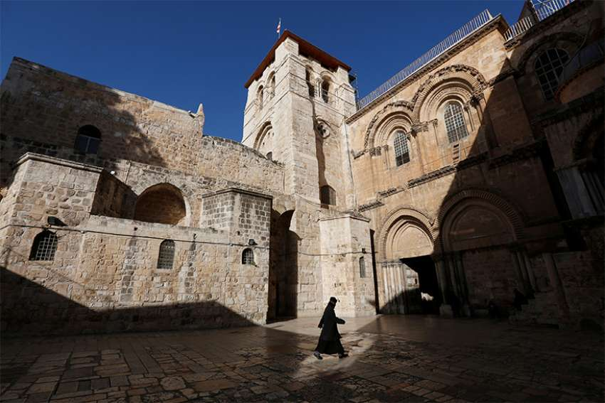 A monk walks outside Jerusalem's Church of the Holy Sepulcher in 2013.