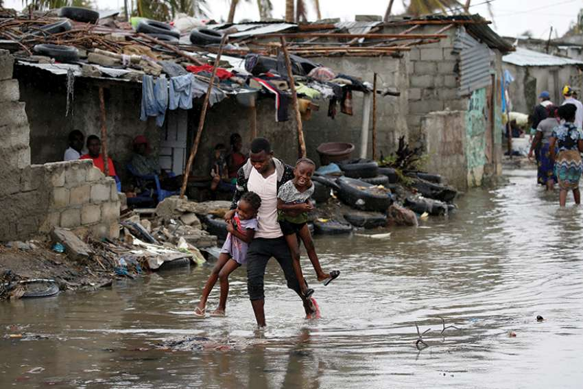A man carries his children through floodwaters in the aftermath of Cyclone Idai in Beira, Mozambique, March 23. More than two million people in Mozambique, Zimbabwe and Malawi have been affected by a cyclone that has killed more than 700 people, with hundreds still missing in Mozambique and Zimbabwe.