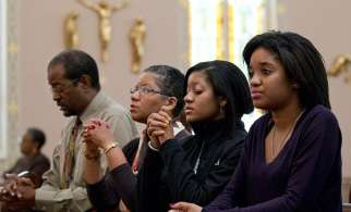A family prays before Sunday Mass starts at St. Joseph's Catholic Church in Alexandria, Va., Nov. 27, 2011.