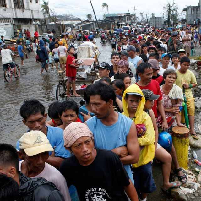 Typhoon victims wait in line for free rice at a businessman's warehouse in Tacloban, Philippines, which was devastated by Super Typhoon Haiyan. Aid agencies faced challenges getting food and water to the hundreds of thousands of Filipinos affected by the storm.