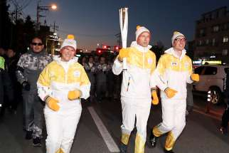 Senior officials of the International Physicians for the Prevention of Nuclear War and the International Campaign to Abolish Nuclear Weapons, both winners of the Nobel Peace Prize, carry the torch of the 2018 Pyeongchang Winter Olympics during a relay in Cheongju, South Korea.