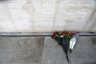 Flowers sit outside New Scotland Yard March 23, the morning after an attack by a man driving a car and wielding a knife left five people dead and dozens injured in London.