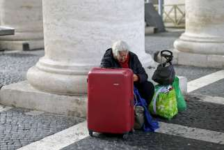 A homeless woman sits with her belongings as she waits for a friend leaving the Vatican following a March 26 visit.