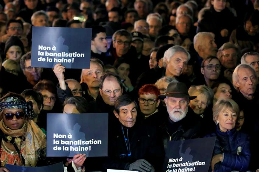 "People attend a national gathering in Paris Feb. 19, 2019, to protest the rise of anti-Semitic attacks. The placards read: ""No to the trivialization of hatred."""