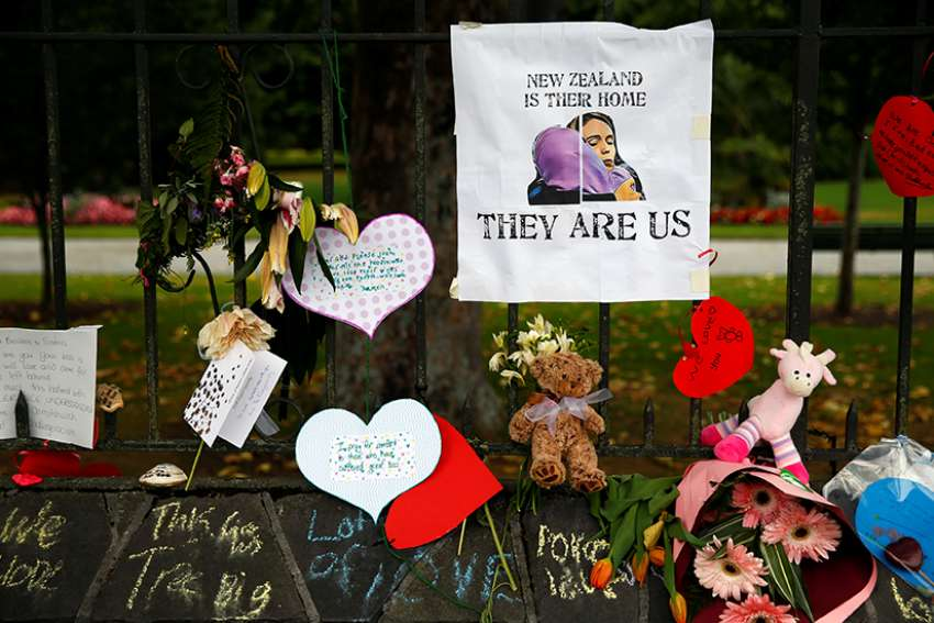 Flowers and signs are seen at the Botanic Gardens in Christchurch, New Zealand, in a makeshift memorial March 18, 2019. Such memorials and prayer services could be found across the country and abroad after two mosque attacks in Christchurch, New Zealand, March 15 that left at least 50 people dead and 20 seriously injured.