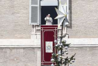 "The Christmas tree is seen as Pope Francis leads the Angelus prayer from the window of his studio overlooking St. Peter's Square at the Vatican Dec. 2. The pope lit an Advent candle as he launched the Christmas campaign, ""Candles for Peace in Syria,"" an initiative of Aid to the Church in Need."