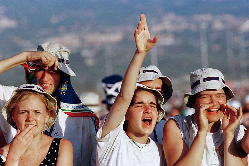 Young people react as the helicopter carrying Pope John Paul II lands at the site of the 2000 World Youth Day prayer vigil outside Rome. He inaugurated World Youth Day 30 years ago. Its international gatherings have drawn hundreds of thousands of people.