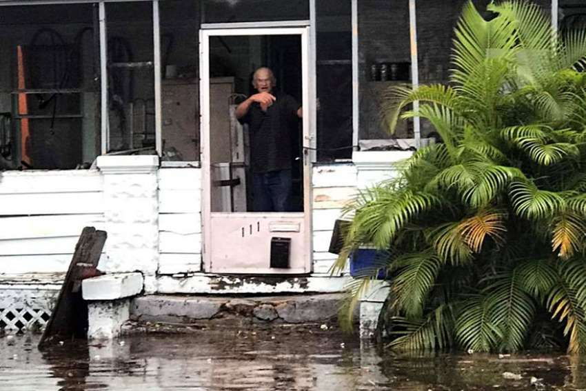A man signals to police officers from a flooded house after Hurricane Irma passed through Daytona Beach, Fla.
