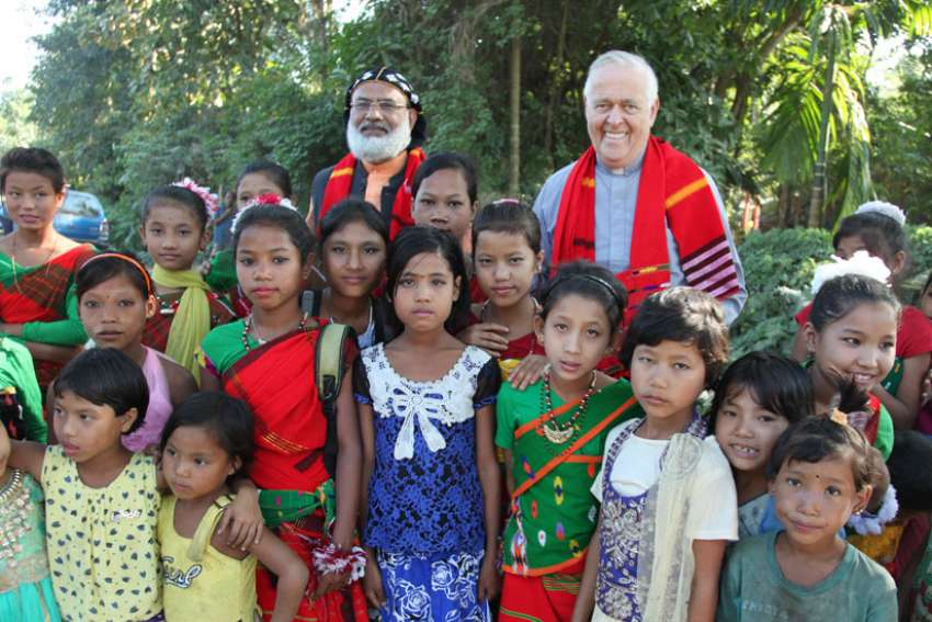 Syro-Malankara Bishop Jacob Barnabas Aerath and Msgr. John E. Kozar, head of the Catholic Near East Welfare Association, pose with village children during a visit to northeast India in late November.