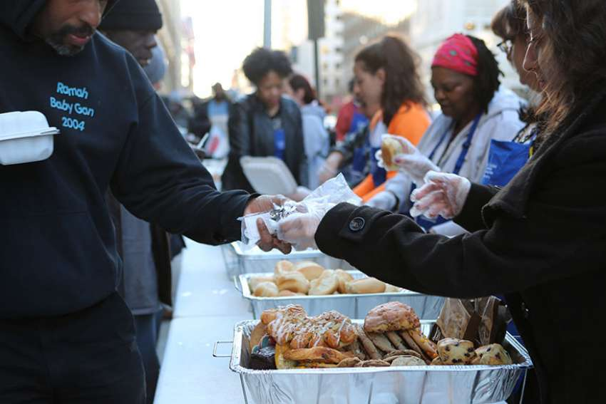 Volunteers with Catholic Charities' St. Maria's meals program in Washington serve dinner March 8 to the homeless.