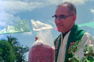 Then-Archbishop Oscar Romero receives a sack of beans from parishioners following Mass outside of a church in San Antonio Los Ranchos in Chalatenango, El Salvador, in 1979. Dominican Father Gustavo Gutierrez, considered by many as the father of liberation theology, said he supports an effort to declare now-St. Oscar Romero a doctor of the Catholic Church.