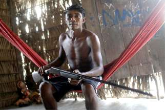 A member of the Tembe indigenous tribe, which is facing a conflict with illegal loggers on its land, holds his gun in Teko-haw indigenous village near Paragominas, Brazil, Sept. 9, 2019. A report released Sept. 24 from the Brazilian bishops' Indigenous Missionary Council shows the number of indigenous murdered last year increased by more than 20% in comparison to 2017.