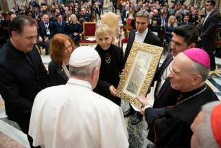 Pope Francis accepts a gift during an audience with a group of international performers at the Vatican Dec. 13, 2019. The performers, including U.S. singer Lionel Richie, were scheduled to perform at the Vatican's Christmas concert the next day.