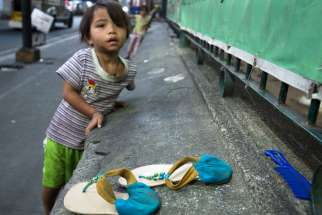 A girl leans against a wall on the streets of Manila, Philippines, Jan. 14.