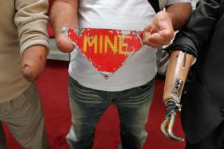Land mine victims hold up a sign against the use of landmines. Pope Francis urged delegates to ban the production and use of landmines.