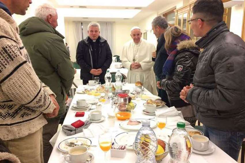 Pope Francis eats breakfast with a group of homeless for his 80th birthday, Dec. 17.