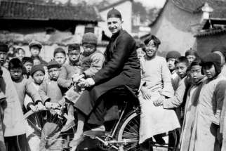 Fr. Craig Strang on his bicycle is given plenty of attention from his pupils in the 1930s.