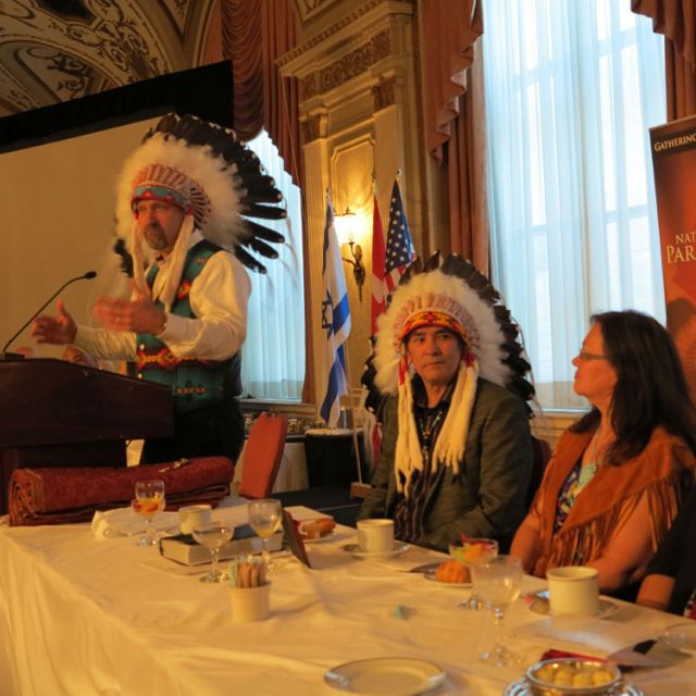 Former Aboriginal Affairs Minister Chuck Strahl at the podium of the National Aboriginal Prayer Breakfast with Honorary Chief Kenny Blacksmith and his wife Louise looking on.